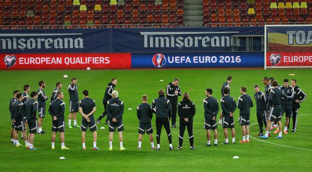 Time to talk: Michael O'Neill briefs his Northern Ireland players ahead of training in Bucharest