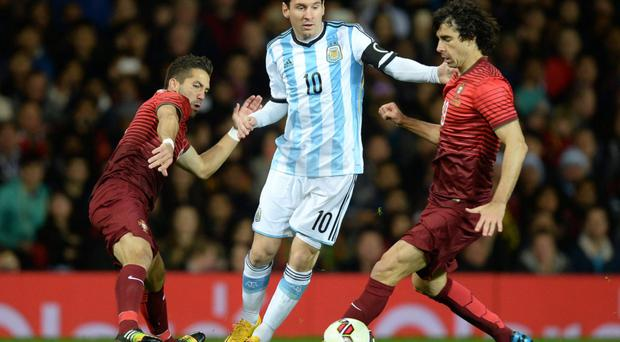 No stopping him: Lionel Messi skips through the challenges of Portugal's Joao Moutinho and Tiago