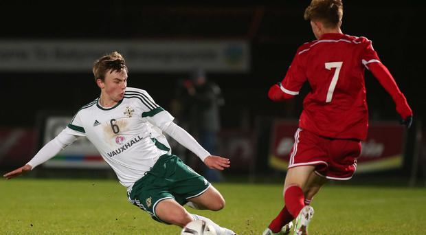 On the slide: Northern Ireland's Liam McKenna wins the ball from Wales' Kieron Proctor