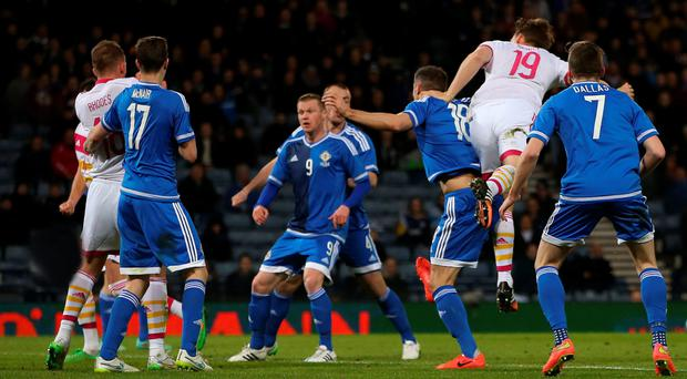Decisive blow: Christophe Berra rises above Aaron Hughes to head home Scotland's winner at Hampden