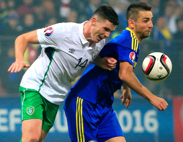 Tough battle: the Republic's Ciaran Clark challenges Bosnia's Vedad Ibisevic last night in Zenica