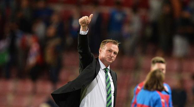 Good start: Michael O'Neill salutes the Northern Ireland fans following last night's final whistle in Prague