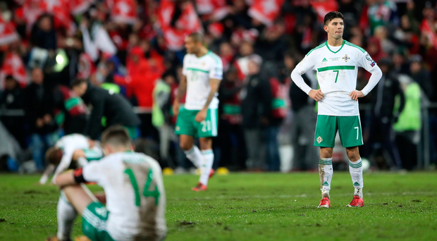 Swiss miss: Jordan Jones shows his obvious disappointment as Northern Ireland team-mates come to terms with defeat in Switzerland