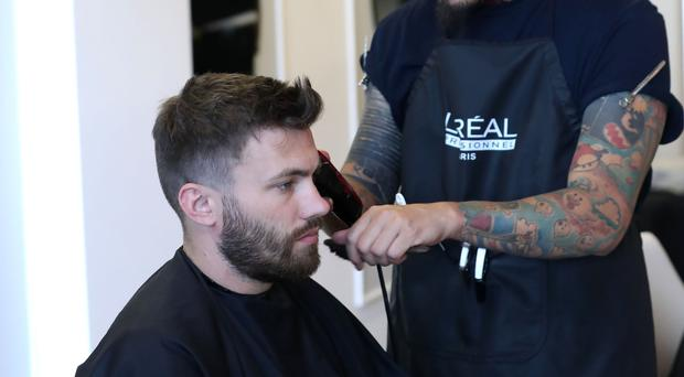 Close shave: Stuart Dallas has a trim at the Northern Ireland team's hotel in San Jose