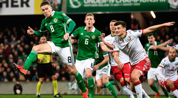 Head man: Steven Davis leaps to win a header during Northern Ireland's victory against Belarus