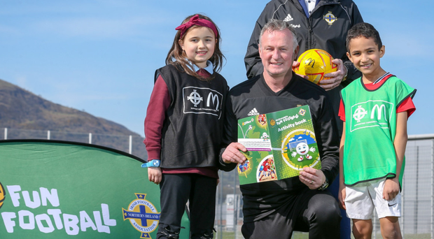 Happy days: Northern Ireland boss Michael O'Neill and McDonald's Football Ambassador Pat Jennings join pupils from Fane Street Primary School at the launch of the McDonald's Fun Football Initiative yesterday