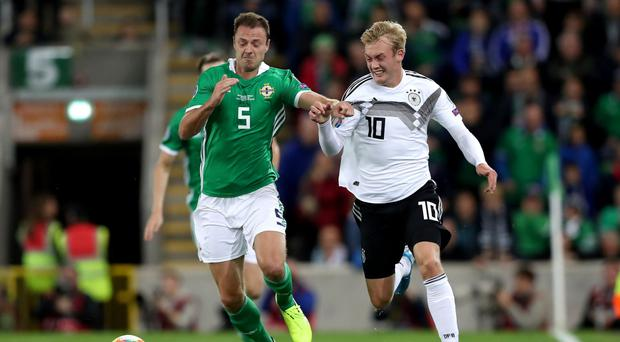 On the run: Northern Ireland's Jonny Evans with Germany's Julian Brandt during Monday night's European Championship Qualifier at Windsor Park