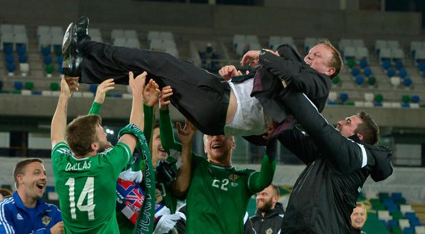 High point: Michael O'Neill is hoisted aloft by his NI players after qualification for Euro 2016