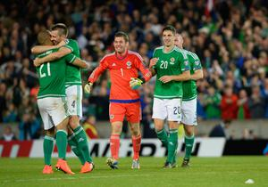 Craig Cathcart (no.20) about to join in the celebrations after Northern Ireland beat Greece to qualify for Euro 2016