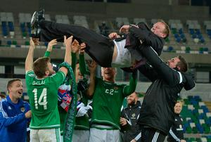 Here we go: Northern Ireland manager Michael O'Neill is thrown in the air by his players as they celebrate clinching qualification