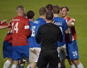 Referee Mervyn Smyth tries to separate Linfield and Glenavon players