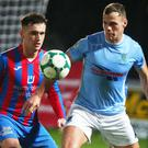 Full focus: Ballymena's Leroy Millar keeps his eye on the ball as Ards' Kyle Cherry closes in