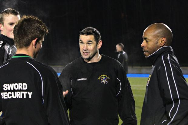 Knockbreda's most high-profile player Miguel Chines (right) gets his instructions from manager Hugh Sinclair (centre)