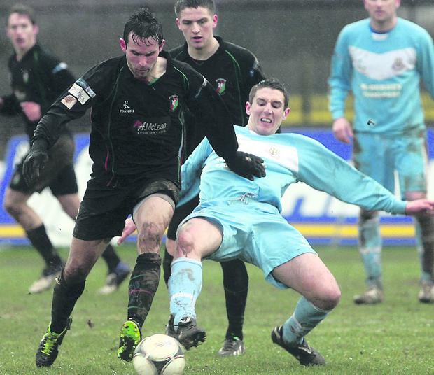 Ballymena United's Gary Thompson challenges Glentoran striker Andy Waterworth