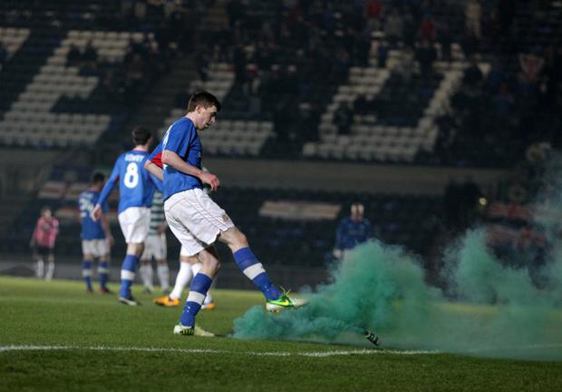 Linfield's Billy Joe Burns deals with a smoke bomb on Monday