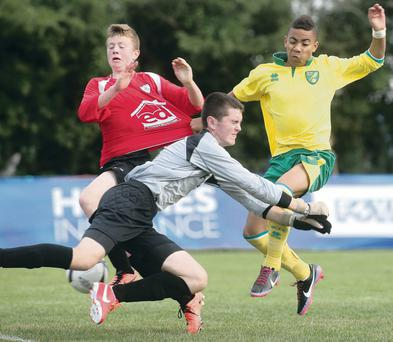 Norwich's Joshua McCammon scores despite the efforts of Derry's Matthew McClelland and James Crawford.