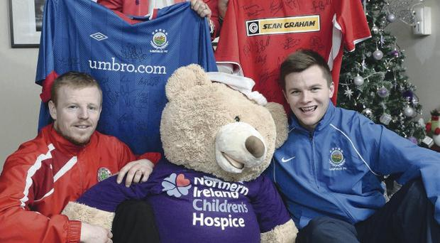Cliftonville ace George McMullan and Linfield's Niall Quinn present signed football shirts to Noreen Kennedy, Community Fundraising Manager and Tina McCrossan, Director of Children and Young People's Services to raise funds for the Northern Ireland Children's Hospice