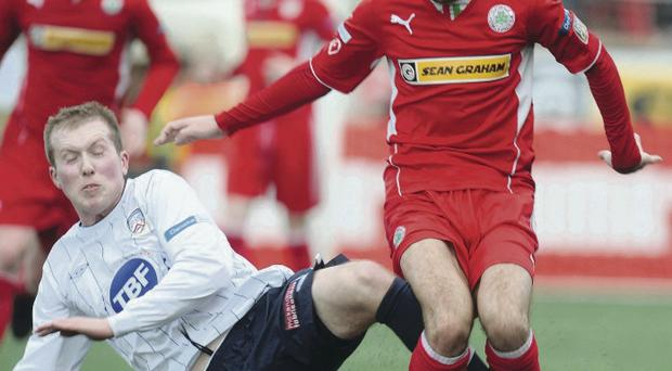 Coleraine winger Stephen Dooley slides in to challenge Cliftonville's Tomas Cosgrove