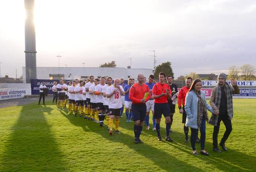 In it together: Mark Farren and wife Terri-Louise lead out the Glenavon and Derry City select sides at the fundraising match staged at Mourneview Park last night
