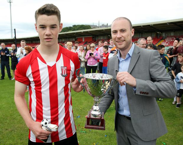 Derry good: Jonathan Robinson of Hughes Insurance presents the U16 Cup to Derry's Ciaran Deery