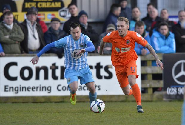 On the run: Linfield's Kirk Millar leaves Warrenpoinit Town's Liam Bagnall trailing in his wake at Milltown