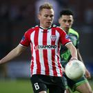 Eye on the ball: Conor McCormack under pressure from Roberto Lopes