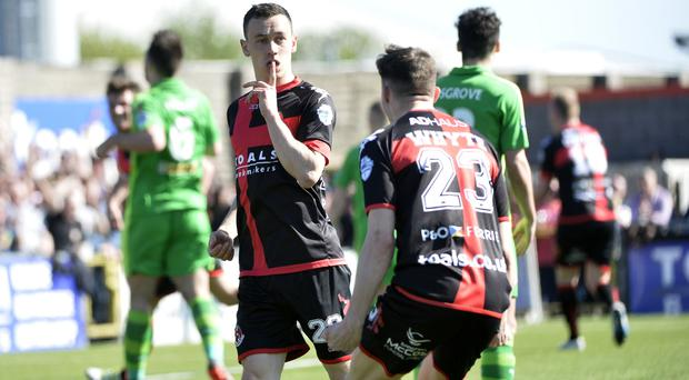 Crowd silenced: Crusaders Paul Heatley celebrates after he lobs the ball over Brian Neeson to draw the sides level at 1-1