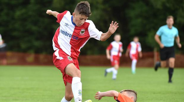 Sliding in: Linfield's Jay Dalzell is held up by Glenavon's Lewis McMaster