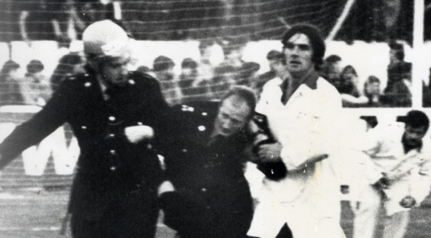 War zone: A Garda is helped away after being injured in the riots at Oriel Park in 1979
