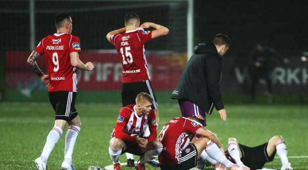 Down and out: Derry's players show their disappointment as Dundalk celebrate with the EA Sports Cup