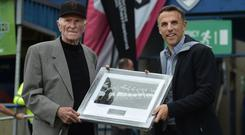 Golden memories: Manchester United legend Harry Gregg is handed a framed photograph of the Busby Babes by former Old Trafford ace Phil Neville at the SuperCupNI last year