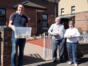 Helping out: Stephen Baxter hands food to residents Jackie and Agnes Salters