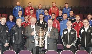 Irish FA President Jim Shaw and former Glentoran star Johnny Jameson – who conducted the draw – show some of the players who will be taking part in the fifth round of the Irish Cup what they are competing for