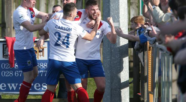 Last gasp: Stephen Lowry takes the adulation of team mates and supporters after his late winner