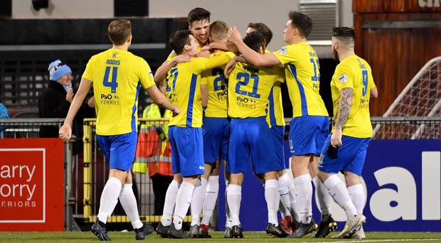 Winning feeling: Ballymena players congratulate Josh Kelly after his late goal