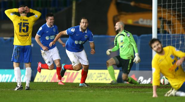 Right on cue: Guy Bates sets off in celebration after bagging Linfield's winner