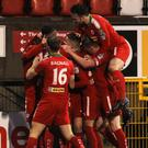 Joy: Stephen Garrett is mobbed after putting Cliftonville ahead