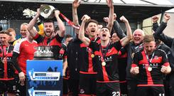 Game over: Crusaders skipper Colin Coates lifts the Gibson Cup after David Cushley scored the goal that sealed the Premiership title