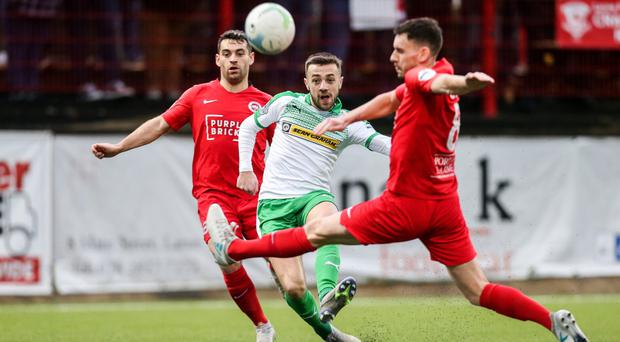 In range: Cliftonville's Conor McMenamin gets a shot away under pressure from Davy McDaid and Mark Randall