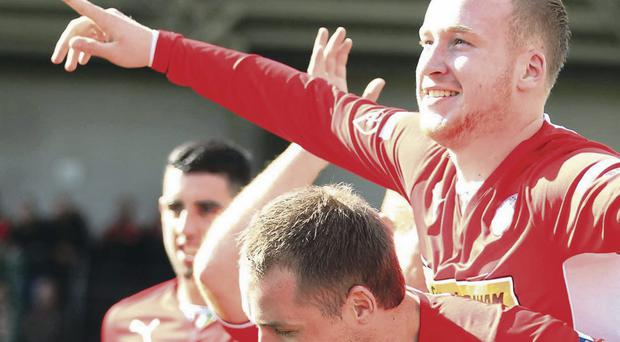 Off and running: Liam Boyce is held aloft by team mate Ciaran Caldwell following Cliftonville's opener