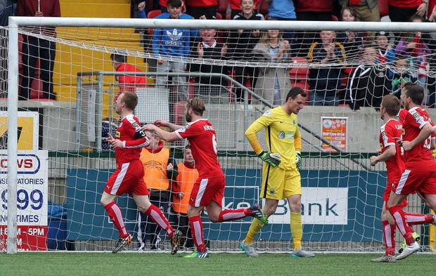 Tasty chip: Reds skipper George McMullan (left) laps up the adulation after getting the better of Linfield keeper Ross Glendinning