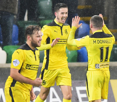 Yellow peril: Jay Donnelly (centre) celebrates his goal against Linfield