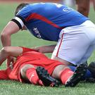 Linfield skipper Jamie Mulgrew tends to injured Cliftonville defender Tomas Cosgrove
