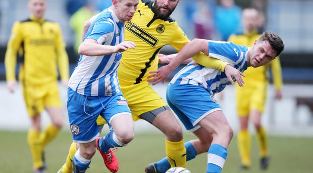 Coleraine's Shane McGinty and John Watt battle with Cliftonville striker Johnny McMurray