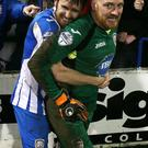 On the spot: Coleraine's shoot-out hero Michael Doherty is embraced by skipper Howard Beverland