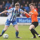 Strength: Jamie McGonigle holds off Glenavon's James Singleton