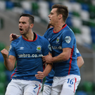 Spot on: Andy Waterworth celebrates with Matthew Clarke after his penalty had set Linfield on their way