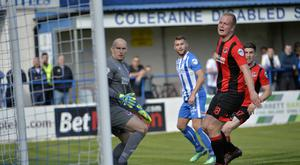 Watching brief: All eyes on the ball as Crusaders striker Jordan Owens slices Stephen Lowry's shot into his own net
