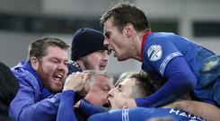 Point made: Joel Cooper is mobbed by Linfield fans and team-mates alike after his late equaliser