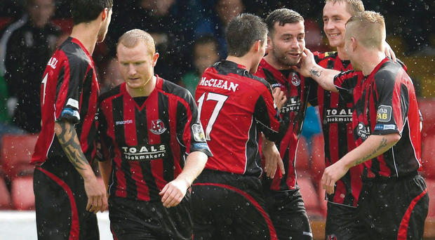 Head boy: Colin Coates is mobbed after nodding home his second goal in Crusaders' 3-0 defeat of Glentoran
